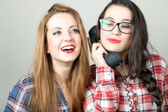 Gossip girls on the phone Stock Photography