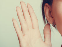 Gossip human eavesdropping with hand to ear. Royalty Free Stock Photography