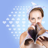 Gossip lady reading the latest womens magazine. Tabloid female reading the weekly gossip column in a womens lifestyle publication folded in a heart shape Royalty Free Stock Photo