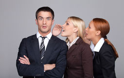The gossip line. Two beautiful young businesswoman telling gossi. Ps to the businessman Royalty Free Stock Photo