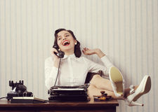 Gossip at phone. Cheerful woman talking on phone at desk Stock Photography