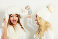 Gossip rumour woman telling secrets to your girlfriend. Relationship gossip. Two multiethnic women in winter clothing whispering secret, funny face expression stock photography