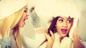 Gossip rumour woman telling secrets to your girlfriend. Relationship gossip. Two multiethnic women in winter clothing whispering secret, funny face expression stock image