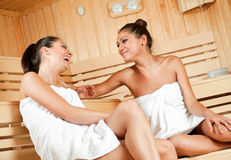 Gossip in sauna. Two beautiful laughing females sitting and talking in sauna royalty free stock image