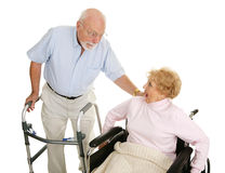 Gossip at the Senior Center. Senior man and woman in a nursing home exchanging gossip. Isolated on white royalty free stock image