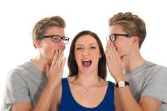 Gossip by twins with a girl. Identically adult male twins whispering in ear from girl isolated over white background Stock Photography