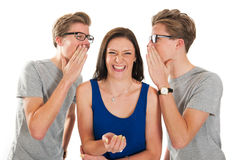 Gossip by twins with a girl. Identically adult male twins whispering in ear from girl isolated over white background Royalty Free Stock Photo