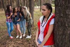 Gossip upset girl forest friendship strife concept. Female rivalry and discussion behind the back. Betrayal and sadness Stock Images