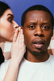 Gossip woman whisper on man ear, tell secret. Gossip white women whispering on ear to black man, closeup. Girl unable to keep important secret. Tattle and stock photo