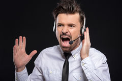 Gossip. Young man is screaming with headphones and microphone on black background Royalty Free Stock Photography