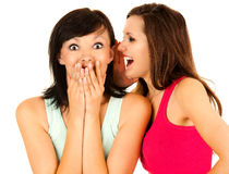 Gossip, young woman whispering to the friends ear Stock Photo