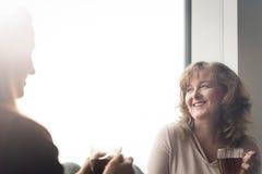 Gossiping матери с дочерью пока имеющ чай Стоковая Фотография