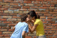 Gossiping. Girl telling secret to boy closeup outdoor stock image