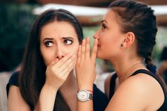 Gossiping Girl Telling Secrets to her Surprised Friend. Young women whispering something confidential to a schoolmate Stock Photo
