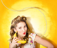 Gossiping retro pin up girl on fruit phone Royalty Free Stock Photos