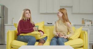 Gossipng de duas jovens mulheres sobre o café no sofá filme