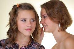Gossips in secret. Two happy young girlfriends talking, gossips in secret stock image