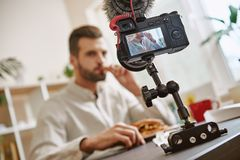 gosto Feche acima da tela da câmara digital com o sanduíche masculino do gosto do blogger do alimento ao gravar o vídeo novo para fotos de stock royalty free