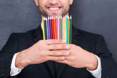 He got creative mind. Close-up of colorful pencils in the hands of smiling businessman standing against blackboard royalty free stock images