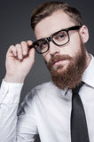 He got creative mind. Handsome young bearded man in shirt and tie adjusting his eyeglasses and looking at camera while standing against grey background stock photos