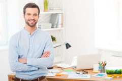 He got creative mind. Handsome young man in shirt keeping arms crossed and smiling at camera while leaning at the desk in office stock photography