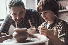 He got creative mind. Little boy drawing on ceramic pot at the pottery class while men in apron standing close to him and smiling stock photos