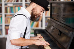 He got creative soul. Handsome young bearded man playing piano and singing Royalty Free Stock Photo