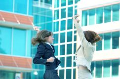 We Got The Deal. Two business women jumping for joy in a high five fashion in celebration for closing the deal Stock Photography