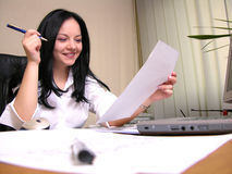 We got the deal!. A smiling young businesswoman signing a contract stock image