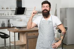 Got fresh idea about his recipe. Happy cook keeping finger raised in kitchen. Bearded chef following recipe to impress royalty free stock image