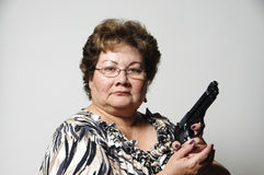 Got gun?. An older Hispanic woman smiling and pointing a gun Stock Images