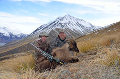 Got him. Two hunters pose with their Himalayan tahr in the Southern Alps of New Zealand Royalty Free Stock Photography