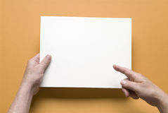 Got a message, put it here. Man's hands holding blank piece of paper on orange background,add your own message Royalty Free Stock Images