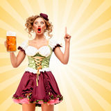 Got a plan. Beautiful smiling sexy Oktoberfest waitress wearing a traditional Bavarian dress dirndl holding a beer mug, and coming up with plan on colorful Royalty Free Stock Photography