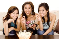 Got Popcorn. Three attractive young asian women sitting on sofa eating popcorn Stock Image
