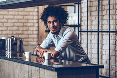 Got some coffee?. Young African man looking at camera with smile while leaning at bar counter with two coffee cups Stock Image