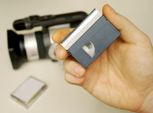 Got It On Tape. A hand holding a MiniDV cassette tape with a camera and tape case in the background Stock Photography