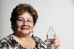 Got water?. An older Hispanic woman holding a bottle of water Royalty Free Stock Photos