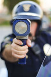 Got you. A police officer holding his radar gun as he tries to catch a speeder Royalty Free Stock Image