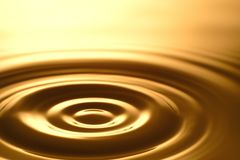 Gota da água - claro e transparente puros da água e da ondinha no fundo do ouro Fotografia de Stock