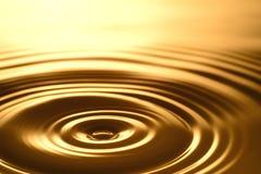 Gota da água - claro e transparente puros da água e da ondinha no fundo do ouro Foto de Stock
