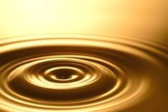 Gota da água - claro e transparente puros da água e da ondinha no fundo do ouro Fotos de Stock Royalty Free