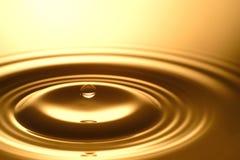 Gota da água - claro e transparente puros da água e da ondinha no fundo do ouro Imagem de Stock