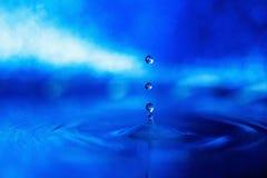 Gota da água em um fundo azul na luz fumarento imagens de stock royalty free
