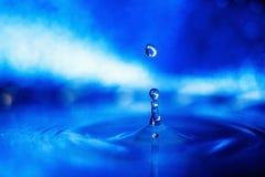 Gota da água em um fundo azul na luz fumarento fotografia de stock royalty free