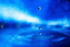 Gota da água em um fundo azul na luz fumarento imagem de stock royalty free