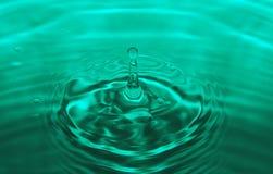 A gota da água que caem fazendo a gota para espirrar e as ondas limpam e conceito fresco Foto de Stock Royalty Free
