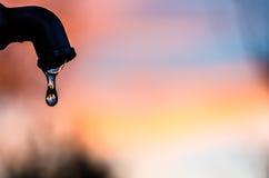 Gota da água que sai de uma torneira do metal com um fundo macio Fotografia de Stock