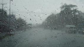 Gota de agua en el frente de cristal de mi coche y limpiadores que trabajan mientras que conduce en el camino metrajes