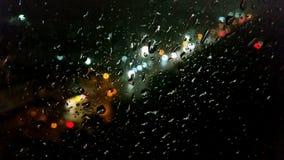 Gota de agua en la ventana con el bokeh de la luz de calle Foto de archivo